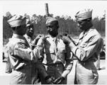 Four soldiers pinning new rank insignia on each other.