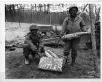 "Two soldiers pose in front of a box labeled ""Easter eggs for Hitler""."